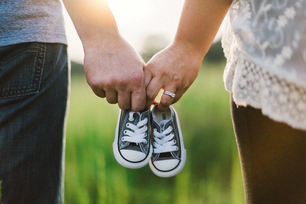 Pärchen Hand in Hand mit schwarzen Baby-Chucks